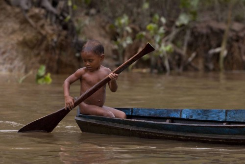 A child paddles in the Aura River, contaminated by the Aura garbage dump, near the mouth of the Amazon in Ananindeua