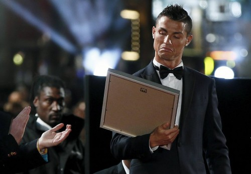 "Soccer player Ronaldo reacts as he receives a certificate on the red carpet at the world premiere of ""Ronaldo"" at Leicester Square in London"