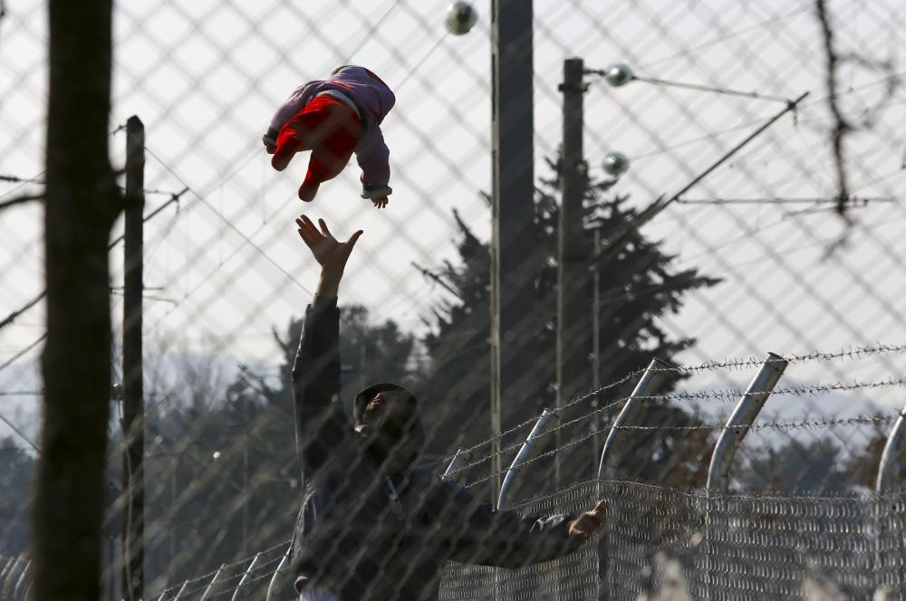 A migrant plays with his baby as they wait to ...