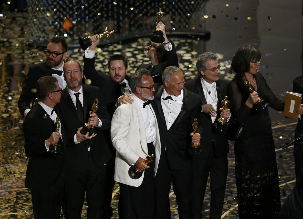 Oscar winners gather on stage after the end of ...